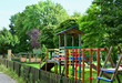 Colourful wooden playground in the park / Colourful wooden playground with a fence in the park
