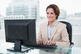 Cheerful businesswoman sitting in front of computer - 202981002