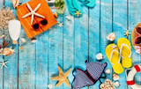 Beach accessories placed on blue wooden planks, top view. - 202981430