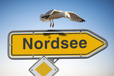 Wegweiser Nordsee Schild, blauer Himmel und Möve im Anflug - 202989622