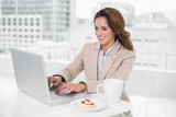 Happy businesswoman using laptop at her desk and having coffee - 203008809
