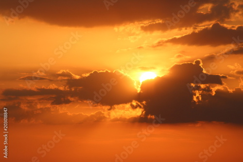 Canvas Baksteen Golden sunset sky with dark cloudscape, sun high in the sky behind clouds