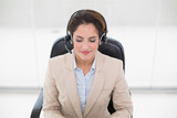 Happy call center agent sitting in swivel chair - 203025494
