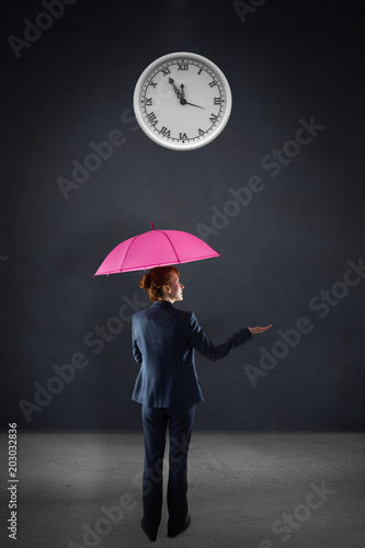Businesswoman with umbrella against grey room