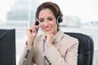 Cheerful businesswoman touching headset