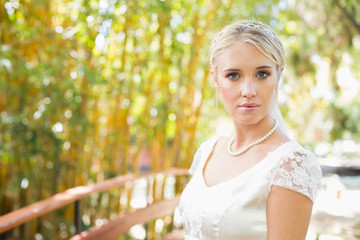 Pretty bride in pearl necklace standing on a bridge © WavebreakmediaMicro