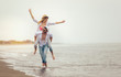 Quadro Happy couple in love on beach summer vacations. Joyful girl piggybacking on young boyfriend having fun.