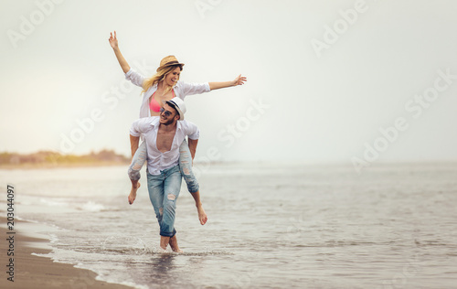 Fototapeta Happy couple in love on beach summer vacations. Joyful girl piggybacking on young boyfriend having fun.