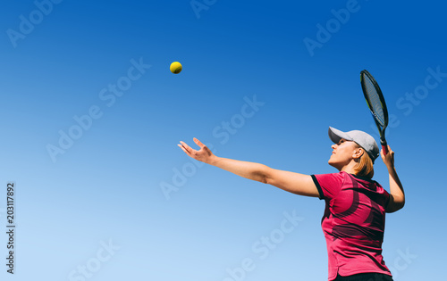 Plexiglas Tennis bottom view young woman, tennis player playing tennis, serving the ball on blue sky with empty space.