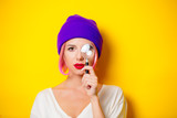 Young girl with pink hair in purple hat holding a magnifier on yellow background - 203121290