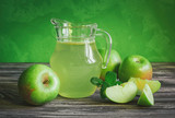 A decanter of apple juice with green apples on a wooden table, close-up