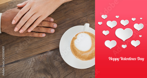 Fototapeta Couple holding hands beside cappuccino against happy valentines day