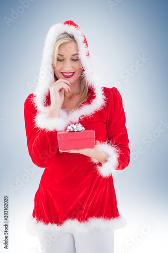 Festive blonde holding a gift on vignette background