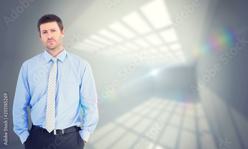 Businessman looking at the camera against room with windows at ceiling