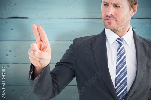 Businessman pointing with his finger against painted blue wooden planks
