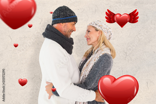 Happy couple in winter fashion embracing against parchment