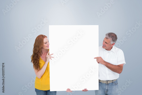 Casual couple showing a poster against grey vignette