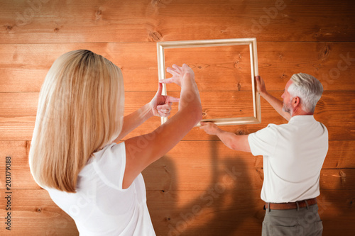 Couple hanging a frame together against overhead of wooden planks