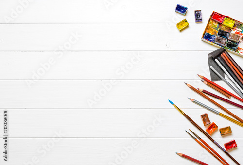 Brushes and paints with pencils on wooden background