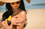 Close - up of Sexy asian woman are Spray Sunscreen , lotion or sunblock to body for prevent UV rays from sunlight Before the sun bathing in the summer or Vacation with sea and bluesky bckground. - 203190494