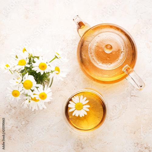 Chamomile ziołowa herbata w teapot i filiżance na beżowym kamiennym tle, odgórny widok