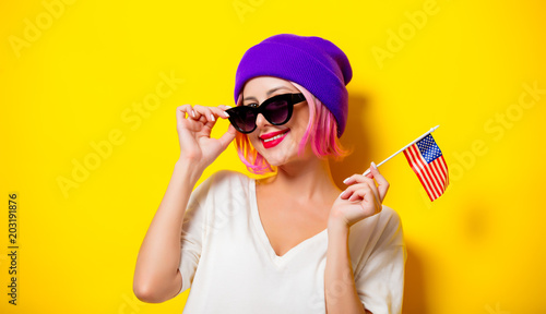 Young girl with pink hair in purple hat and sunglasses holding United States flag on yellow background