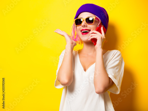 Foto Murales Young girl with pink hair in purple hat talking by mobile phone on yellow background