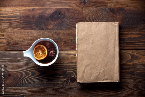 Biała filiżanka z herbatą i książką na drewnianym stole. Wysoki kąt widzenia