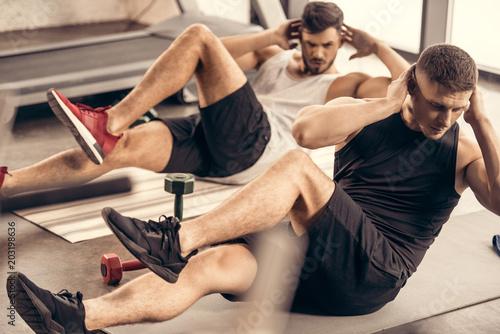 Sticker handsome sportsmen doing sit ups together in gym