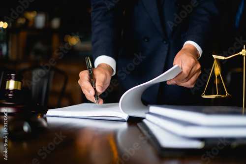 Close up lawyer businessman working or reading lawbook in office workplace for consultant lawyer concept. © itchaznong