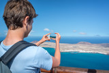 Young man taking pictures with his smartphone, in Lanzarote, Spain - 203207889