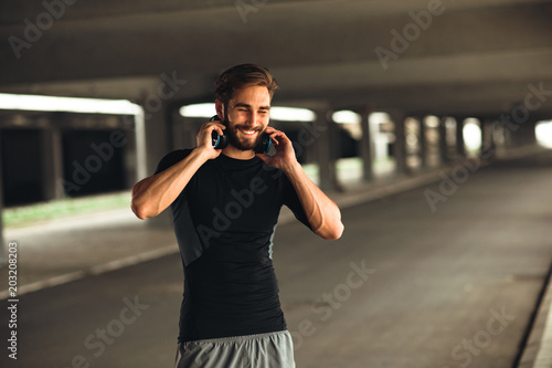 Wall mural Young man resting and listen to music after jogging