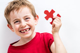 laughing toothless boy finding jigsaw for concept of fun education - 203213814