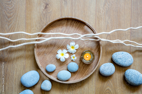 Plexiglas Spa zen flow of pebbles, candle, flowers and twigs over wood