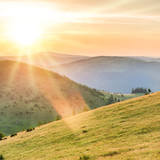 Sunset in the mountains with forest, green grass and big shining sun on dramatic sky
