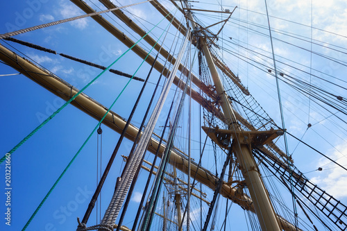 Canvas Schip Masts of a sailing ship with the lowered sails with blue sky on the background.