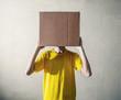 persona con in testa una scatola di cartone