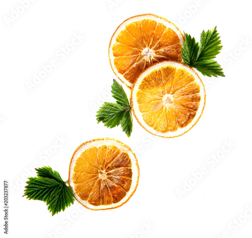 Wysuszeni pomarańczowi round plasterki z zielonymi liśćmi na odosobnionym białym tle.