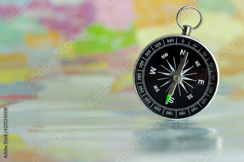 Fototapeta Compass laid on a paper map. The concept of travel.