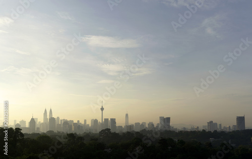 panorama view of beautiful kuala lumpur cityscape skyline in the hazy or foggy morning enviroment and buildings in silhouette with copy space