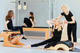 Fitness, sport, training and people concept - group of four people doing pilates exercises with chair, barrel, small barrel, reformer, cadillac - different equipment in modern eco studio interior.