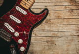 Close-up of electric guitar lying on vintage wood background, with copy space - 203275869