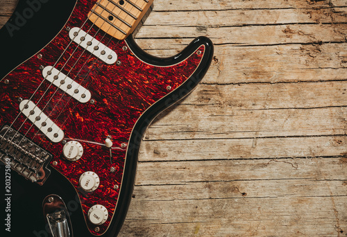 Close-up of electric guitar lying on vintage wood background, with copy space