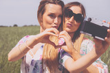 freundinnen machen selfie fotos mit einer retro kamera