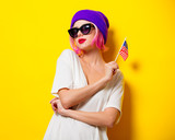 Young girl with pink hair in purple hat and sunglasses holding United States flag on yellow background - 203293231