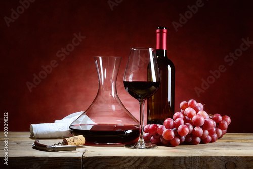 Fototapeta Red wine glass with bunch of grapes and decanter