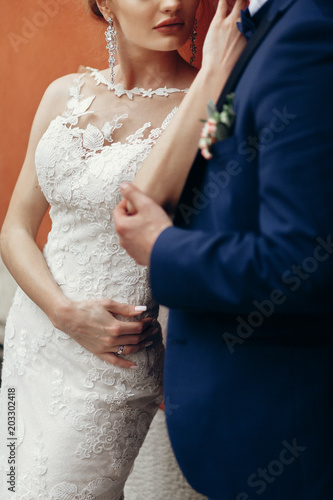 Sensual newlywed couple posing near wall outdoors in the city, wedding celebration, happy bride and groom holding hands portrait, marriage concept