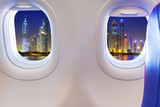 Airplane windows with Dubai skyscrapers view. Travel to Emirates