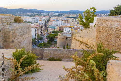 Panoramic view from medieval fortress on old town, streets and roofs of houses and mountains of Ibiza Town, Balearic Islands, Spain