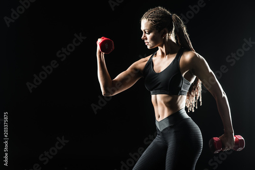 Fototapeta Profile view of beautiful athletic girl exercising. Fitness concept